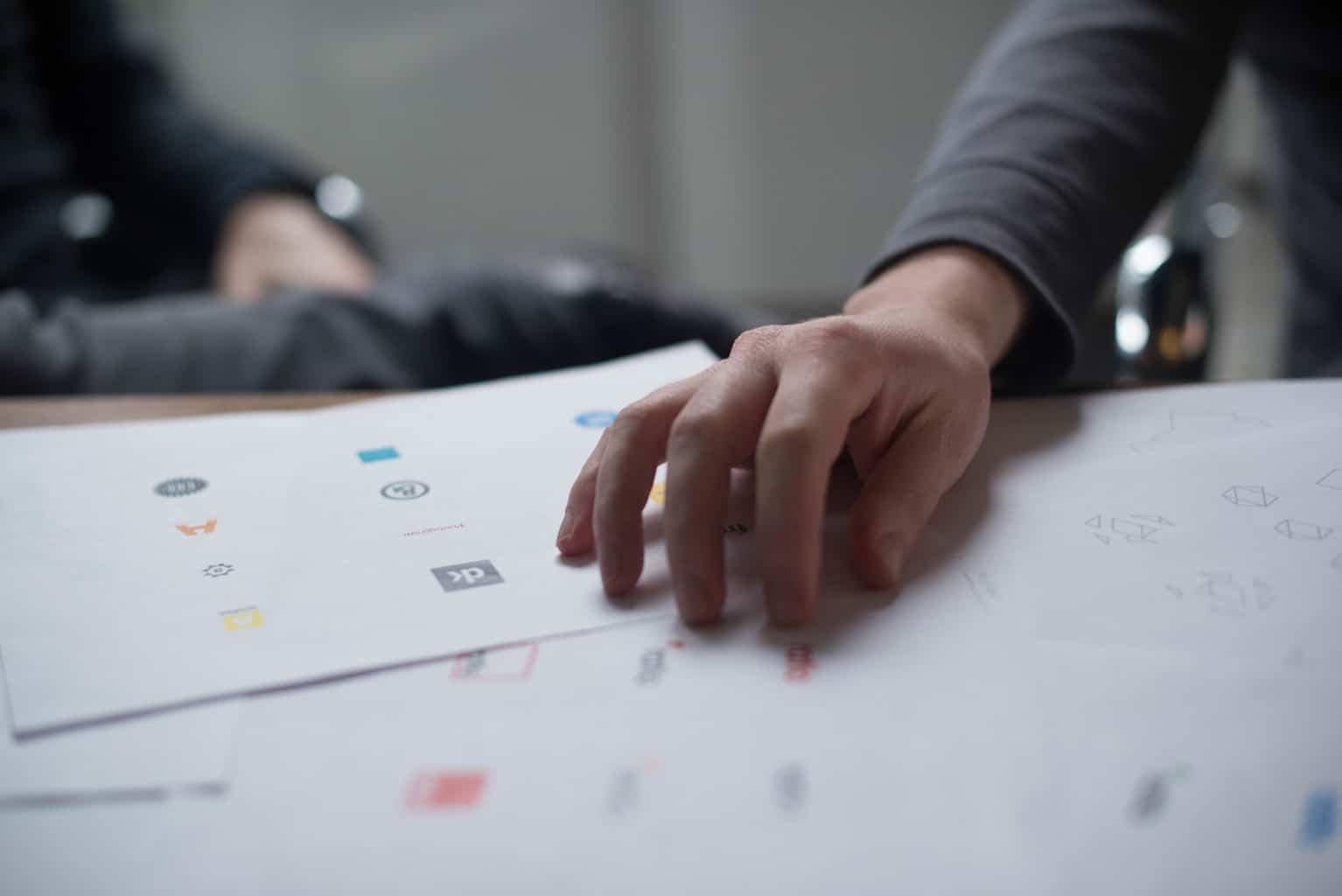 Logo designer hand on paper
