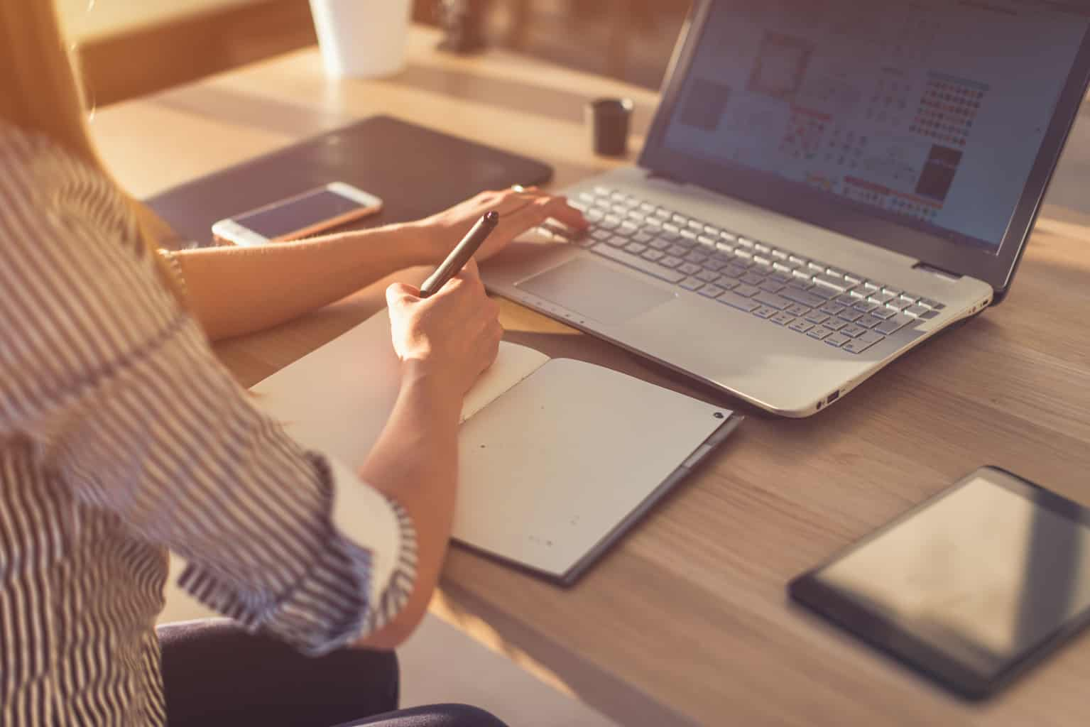 Female designer using laptop, sketching at blank notepad. Woman hand writing in notebook on wooden desk.