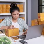 small-online-business-owner-woman-working-with-laptop-prepare-parcel-boxes-deliver-customer